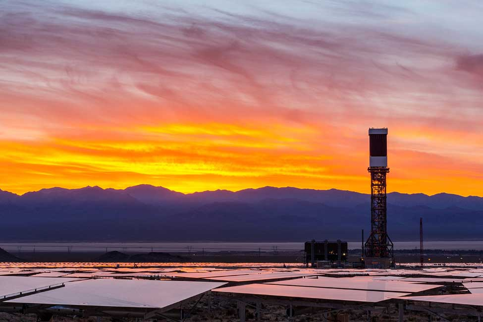 The sun rises over one of Ivanpah's towers