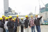 a group of students in hard hats on a tour at a shipyard