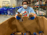 a Bechtel employee poses with a box of donated loaves of bread