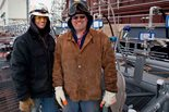 Two craft workers smiling in front of construction site.