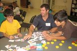 a Bechtel employee helps two young boys complete a puzzle