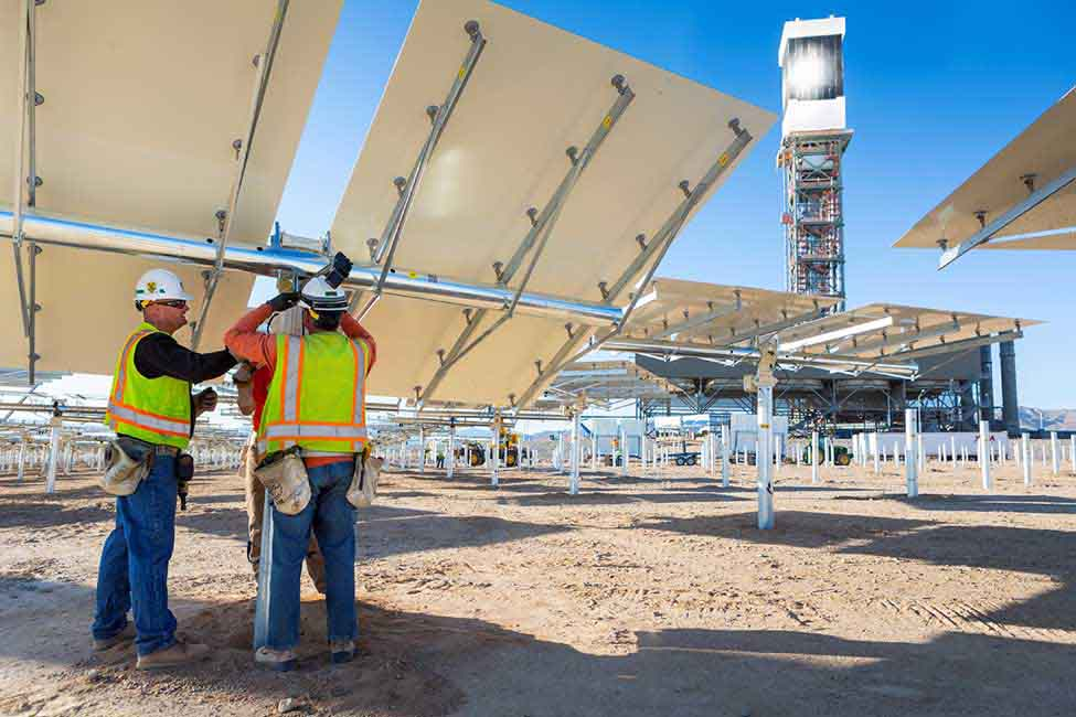 Workers install one of the project's 173,500 heliostats