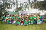 A large group of volunteers in matching green shirts pose in front of a Bechtel sponsored charity construction project