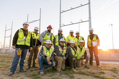 eleven workers pose in front of a transformer yard