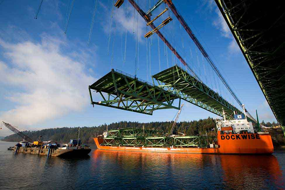 Two gantry cranes were used to hoist the bridge's 46 steel road deck segments from a barge and install them