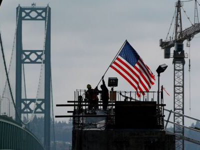 construction workers hoist an American flag on a project site