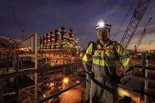 employee posing in front of Wheatstone facility at night