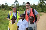 two Bechtel employees pose with a group of young children