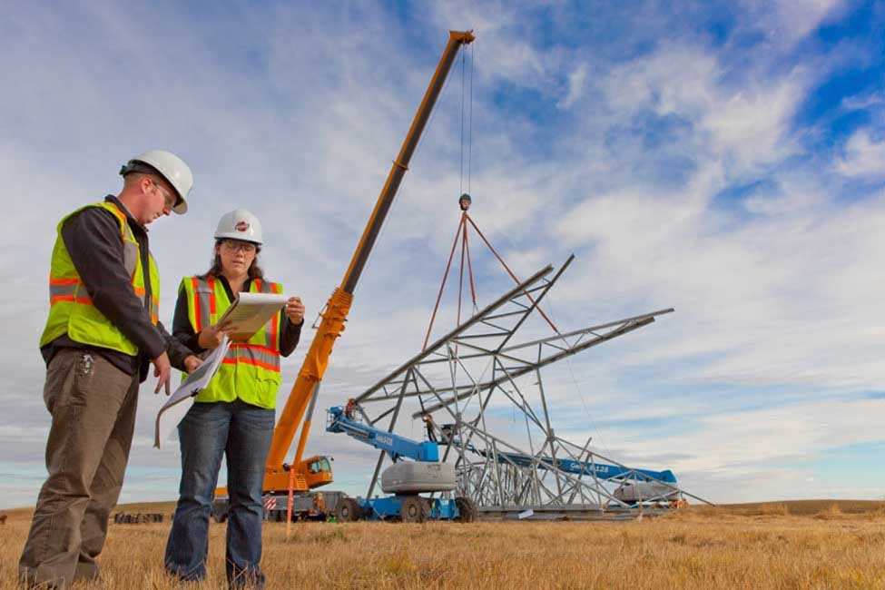 Project members oversee the assembly of transmission towers