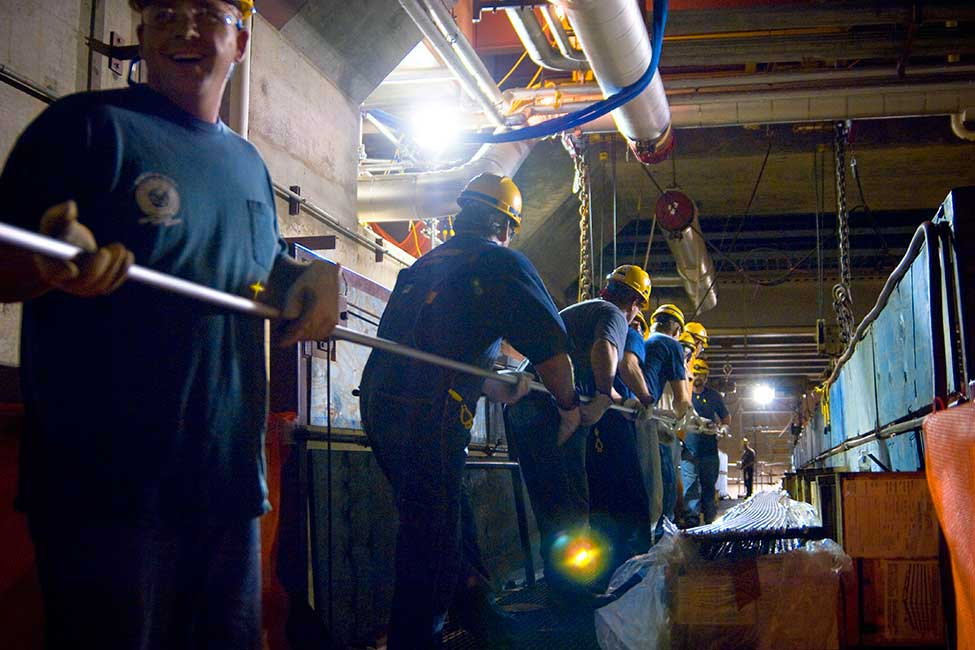Line of workers in protective equipment carrying a long thin piece of pipe