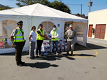 Bechtel employees and uniformed soldiers shake hands in front of a tent storing donated food
