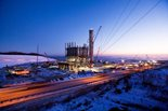 Power plant at night with snow covering ground.