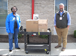 man and women standing next to cart with donated materials