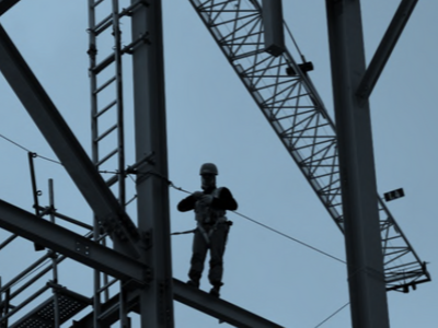 a picture of a worker high up in the air, standing on scaffolding