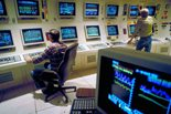 Computer control room with two men monitoring all the screens.