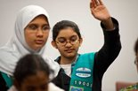 Two young women dressed as girl scouts participate in a discussion