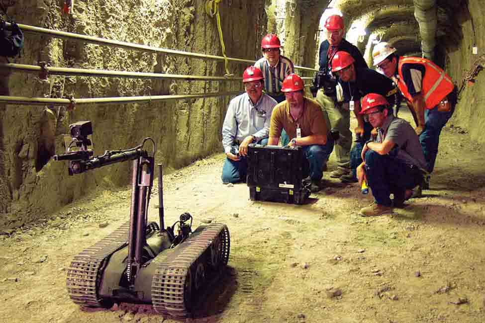 Team members operate one of the facility's robots