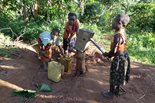 three young children fill up water jugs at a hand-operated pump
