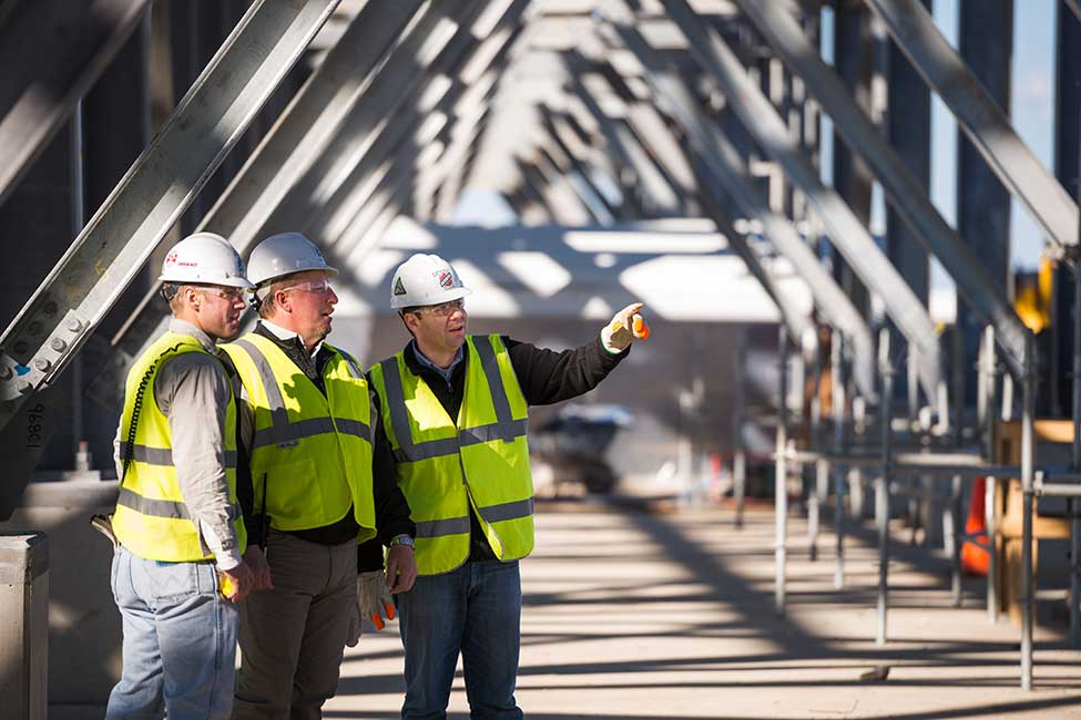 Workers review the project's progress
