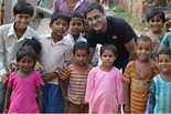 A group of young children pose with a Bechtel employee