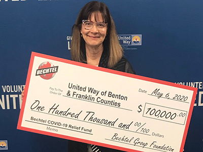 LoAnn Ayers, president and CEO of the United Way of Benton and Franklin Counties holding $100,000 check from Bechtel Group Foundation